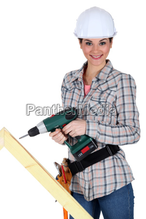 woman drilling into plank of wood
