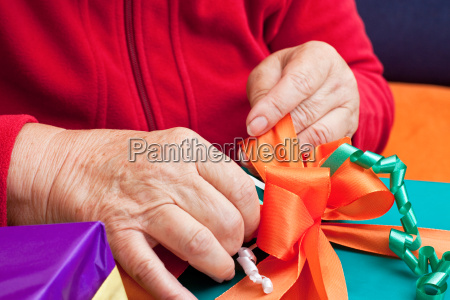 senior sits and packs gifts in