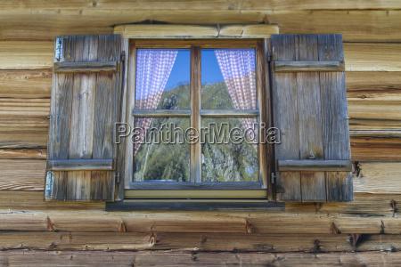 holzhuette mit fenster in den alpen