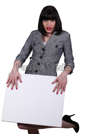 attractive brunette stood with blank panel
