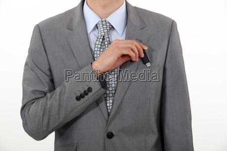 a businessman putting his usb key