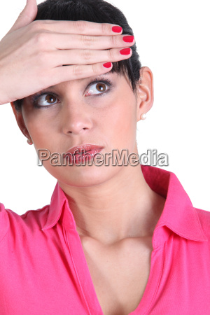 young woman touching her forehead