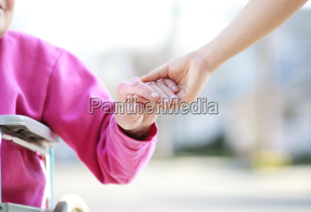 aeltere dame im rollstuhl haende halten