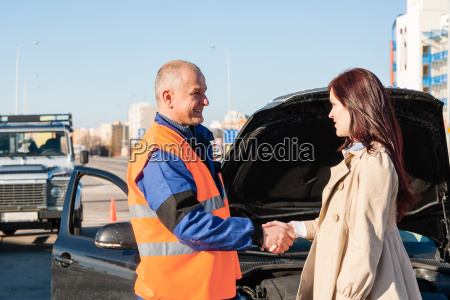 woman greeting mechanic after her car