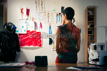female fashion designer contemplating drawings in