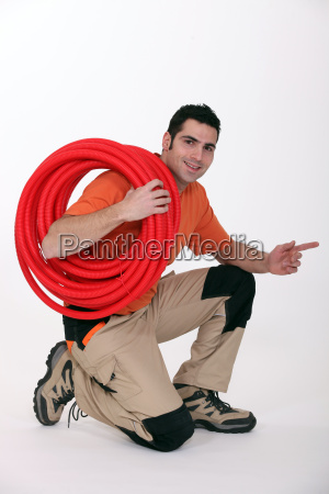young plumber pointing to his side