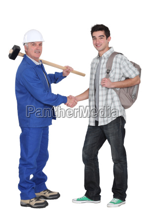 mature craftsman shaking hands with apprentice