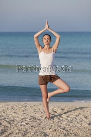 frau macht yoga sport am strand