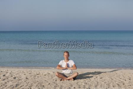 mann macht yoga sport am strand