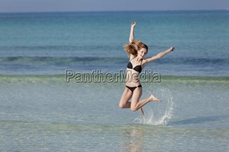woman with bikini jumping in the