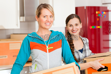 two women with moving box when