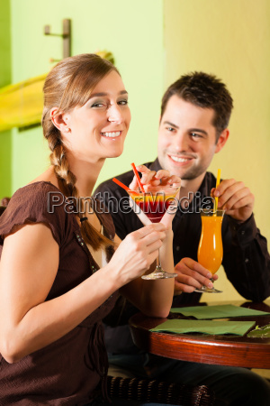 young couple drinking cocktails in a