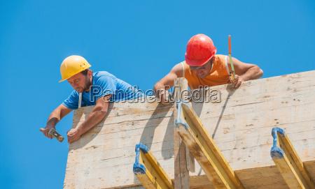 bauarbeiter nageln zementschalung an ort und