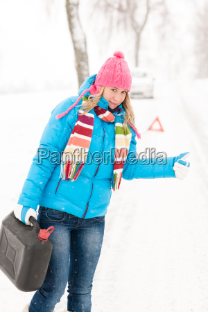 woman hitchhiking on road snow gas