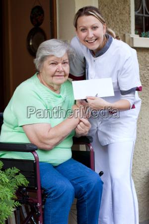 pflegerin und patientin im rollstuhl halten