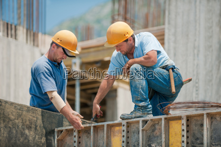 two construction workers installing concrete formwork