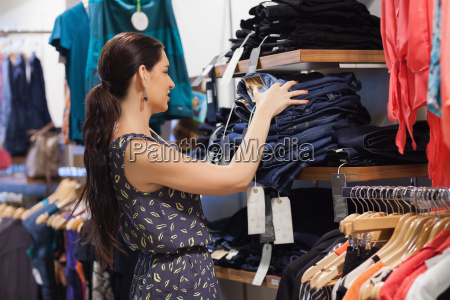 woman stapeln jeans auf dem regal