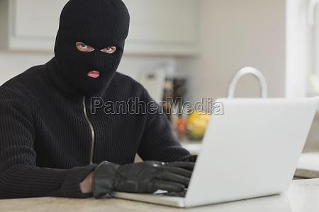 einbrecher mit laptop sitzt in der