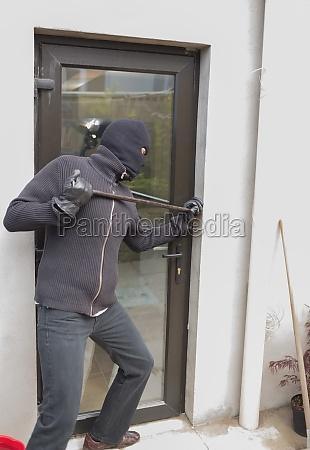 burglar breaking door from outside with