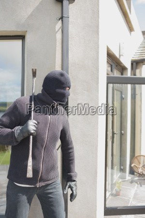 robber hiding behind a wall with