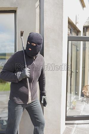 burglar hiding behind wall with crow