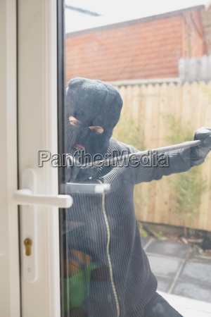 buglar opening door from outside with