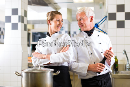 two cooks team in restaurant kitchen