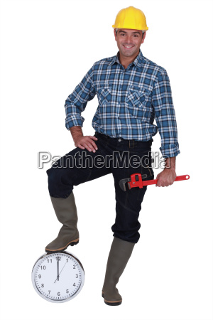 happy laborer leaning on a clock
