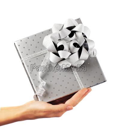 weibliche hand haelt silber geschenk box