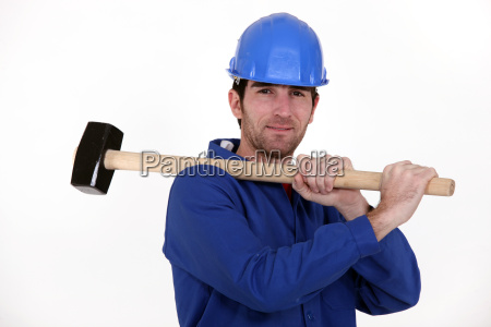 worker carrying a mallet on his