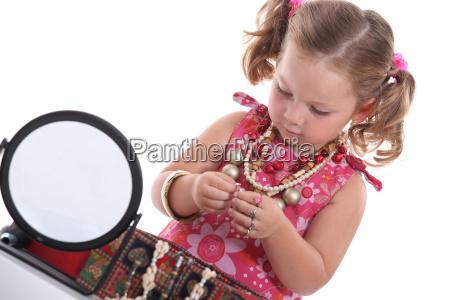 kleines maedchen mit ketten und spiegel