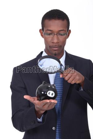man observing a piggy bank