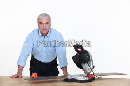 grey haired man with circular saw