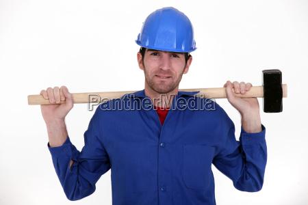craftsman in blue overalls holding huge