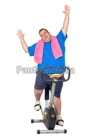 dicker mann in einem statischen fahrrad