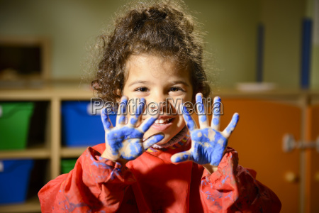 happy little girl painting with hands