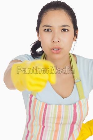 beschuldigende frau in schuerze und gummihandschuhe