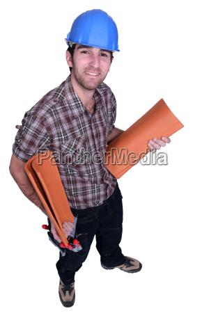 handwerker haelt dachziegel