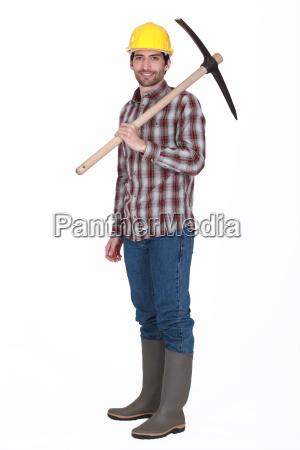 labourer carrying a pickaxe