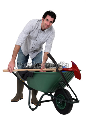 smiling man pushing a wheelbarrow studio