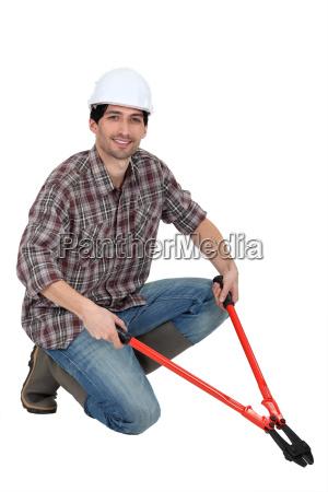 mann kniet mit bolzenschneider