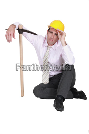 businessman wearing helmet and holding a