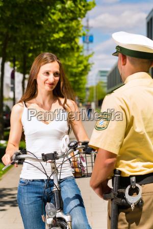 frau auf fahrrad mit polizist in