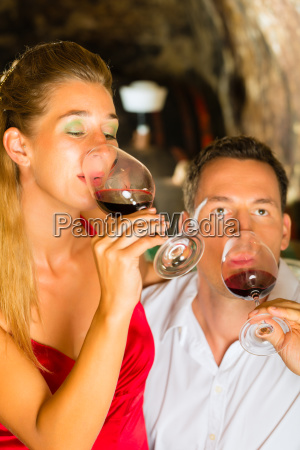 man and woman taste wine in