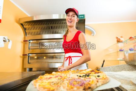frau haelt eine ganze pizza in