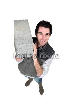 man carrying breeze block