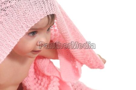 active baby under a pink blanket