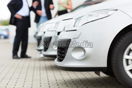 autohaendler und kunden schauen ein auto