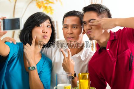 asiatische freunde machen foto mit handy