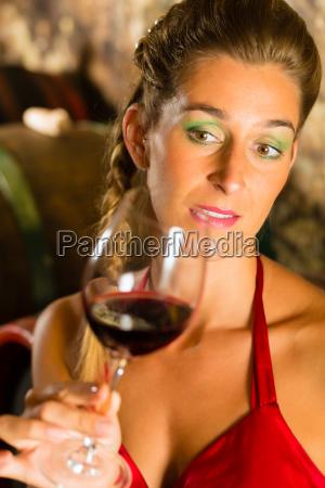 woman looks wineglass in wine cellar